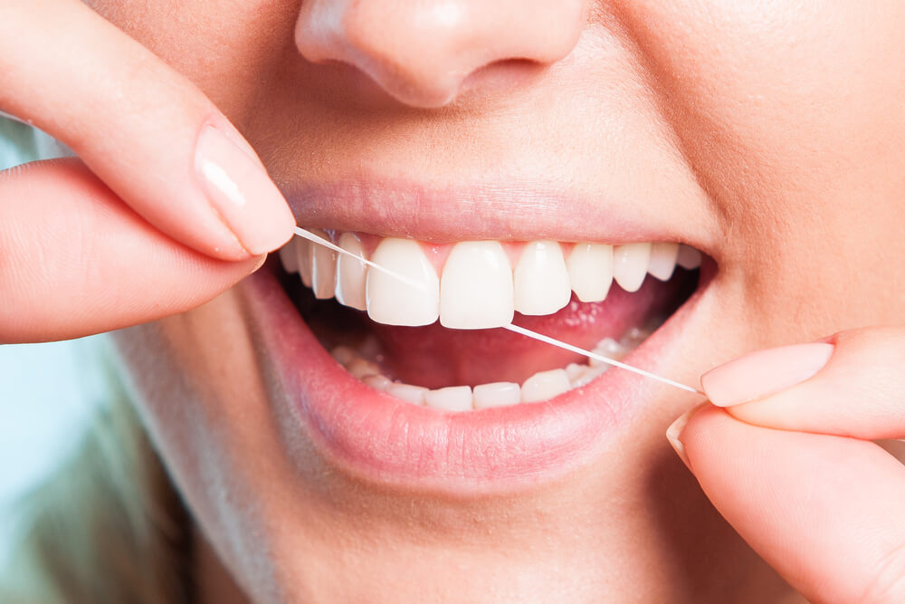 up-close set of teeth being flossed